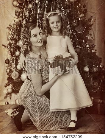Family portrait of child with mother receiving gift near Christmas tree. Black and white retro on yellow old paper.