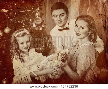 Portrait of family with children dressing Christmas tree. Father hugs his wife and daughter. Black and white retro.