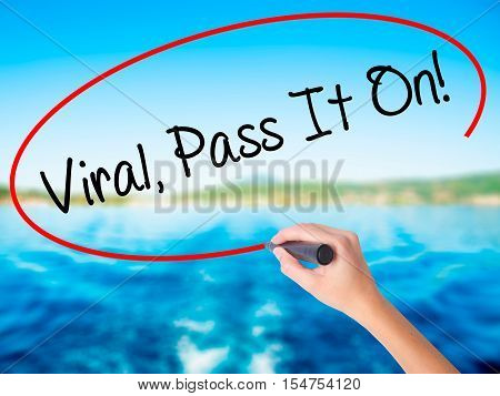 Woman Hand Writing Viral, Pass It On!  With A Marker Over Transparent Board.
