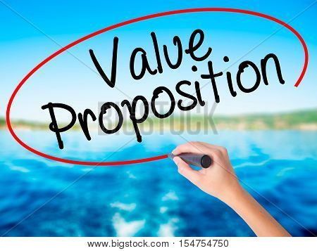 Woman Hand Writing Value Proposition With A Marker Over Transparent Board
