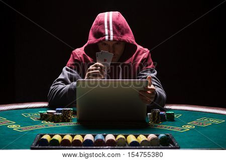 Online poker players sitting at the table. He plays on laptop. The man in the hood, do not see the face. It shows two aces, a winning combination