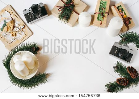 Christmas and New Year background with vintage film camera, white candles, tray, gifts, spruce cones and braches on white background. Top view, flat lay