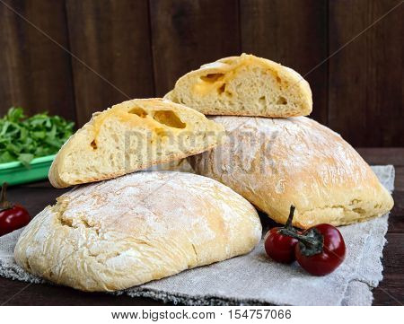 Ciabatta with cheese stuffing - freshly baked Italian white bread on a dark wooden background. For the preparation of sandwiches.