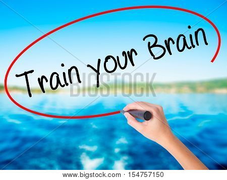 Woman Hand Writing Train Your Brain With A Marker Over Transparent Board