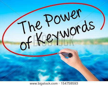Woman Hand Writing The Power Of Keywords With A Marker Over Transparent Board