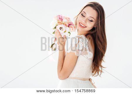 Portrait of happy bride with bouquet. stands sideways