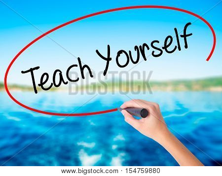 Woman Hand Writing Teach Yourself  With A Marker Over Transparent Board