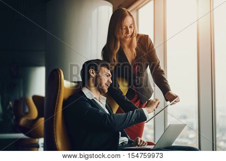 Businesswoman in red dress and jacket showing information on screen of her tablet to her colleague businessman on yellow armchair in formal suit with white laptop luxury office