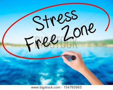 Woman Hand Writing Stress Free Zone With A Marker Over Transparent Board