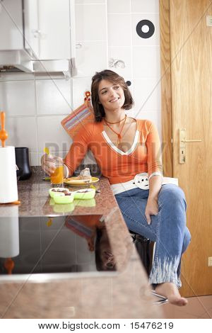 beautiful woman eating her breakfast and looking natural at her kitchen (selective focus with shallow DOF)