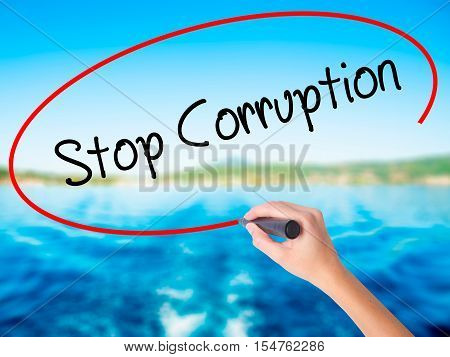 Woman Hand Writing Stop Corruption With A Marker Over Transparent Board.