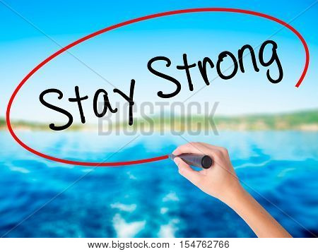 Woman Hand Writing Stay Strong With A Marker Over Transparent Board.