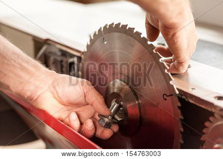 Woodworker Changing A Sawblade By Hand