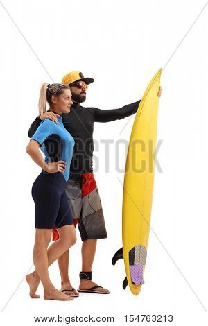 Full length profile shot of a male and female surfer posing with a surfboard isolated on white background