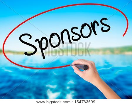 Woman Hand Writing Sponsors  With A Marker Over Transparent Board