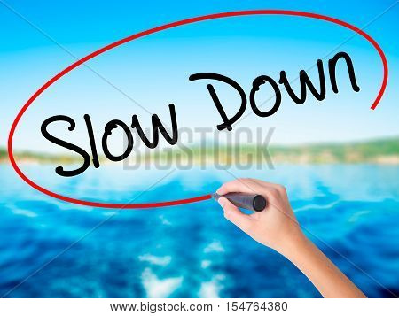 Woman Hand Writing Slow Down With A Marker Over Transparent Board