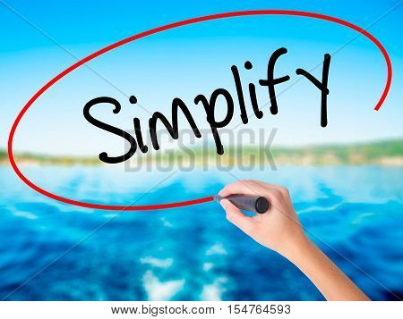 Woman Hand Writing Simplify With A Marker Over Transparent Board