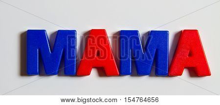 Russian language, the word Mother is laid out from plastic letters with a magnet. Cyrillic.