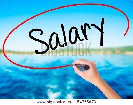 Woman Hand Writing Salary  With A Marker Over Transparent Board
