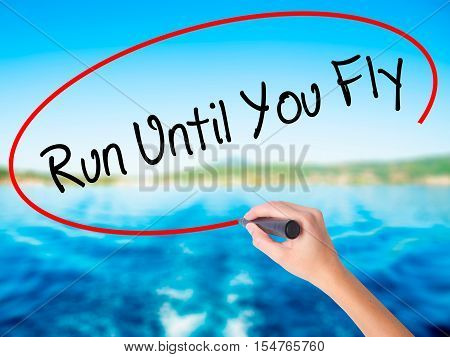 Woman Hand Writing Run Until You Fly  With A Marker Over Transparent Board