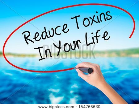 Woman Hand Writing Reduce Toxins In Your Life With A Marker Over Transparent Board