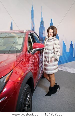 MOSCOW - FEB 14, 2015: Beautiful girl (with model release) in a fur standing near the red car in the salon  in the salon on Russian sixth test drive Lexus Master Class
