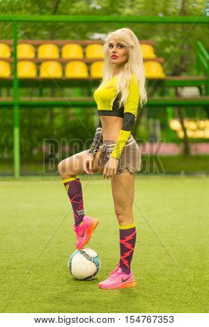 MOSCOW - JUL 16, 2015: Beautiful blonde woman with long hair in top with ball on soccer field, looking at camera
