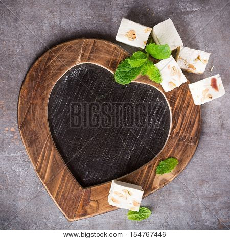 Valentines Day background with vintage slate chalk board in heart form and soft nougat blocks with peanuts and fruit with copy space for text. Valentine's Day concept. View from above.