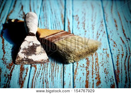 Paint Brush and Trowel scraping on the wood Table Paint by cyan color