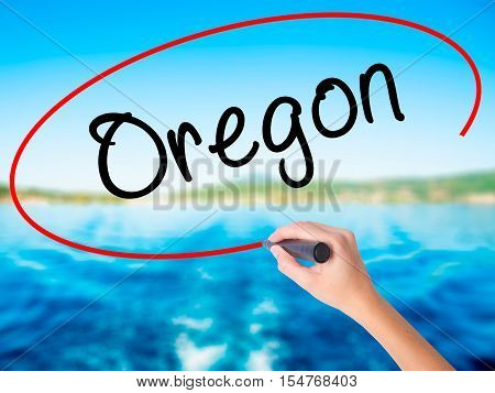 Woman Hand Writing Oregon With A Marker Over Transparent Board