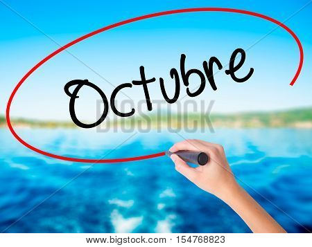 "Woman Hand Writing ""octubre"" (in Spanish: October) With A Marker Over Transparent Board"