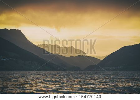 Beautiful view of the lake Resia. Dramatic sky and colorful sunset. Alps, Italy, Europe. Toned like Instagram filter