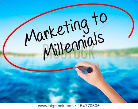 Woman Hand Writing Marketing To Millennials With A Marker Over Transparent Board