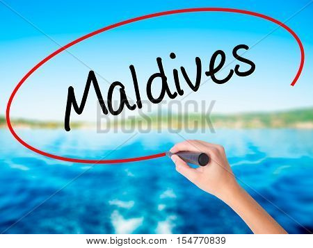 Woman Hand Writing Maldives  With A Marker Over Transparent Board
