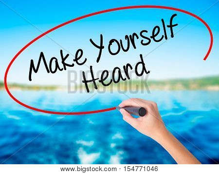 Woman Hand Writing Make Yourself Heard With A Marker Over Transparent Board