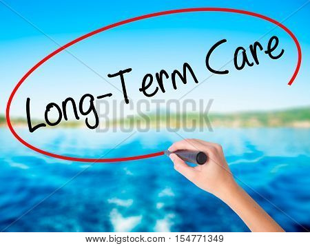 Woman Hand Writing Long-term Care With A Marker Over Transparent Board