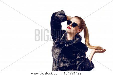 Portrait of attractive blonde model in fur coat and black sunglasses. Isolate