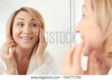 Senior woman doing facial anti aging massage near mirror