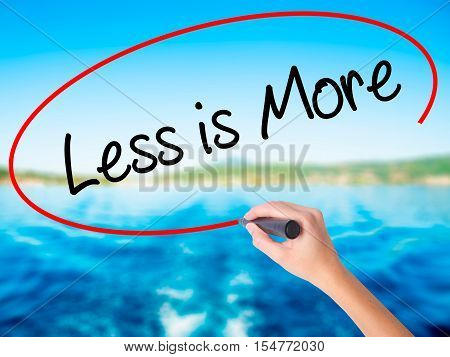 Woman Hand Writing Less Is More With A Marker Over Transparent Board