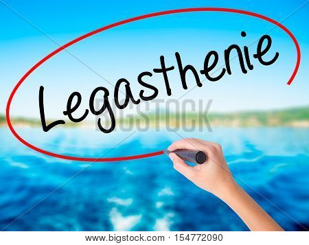 Woman Hand Writing Legasthenie (dyslexia In German) With A Marker Over Transparent Board.