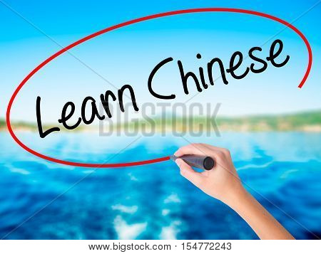 Woman Hand Writing Learn Chinese With A Marker Over Transparent Board.