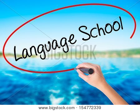 Woman Hand Writing Language School With A Marker Over Transparent Board