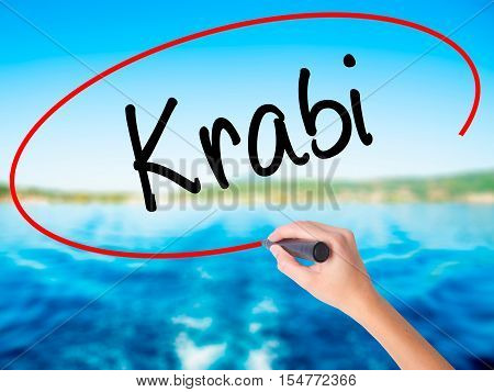 Woman Hand Writing Krabi  With A Marker Over Transparent Board.