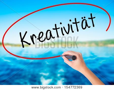 Woman Hand Writing Kreativität (creativity In German)   With A Marker Over Transparent Board