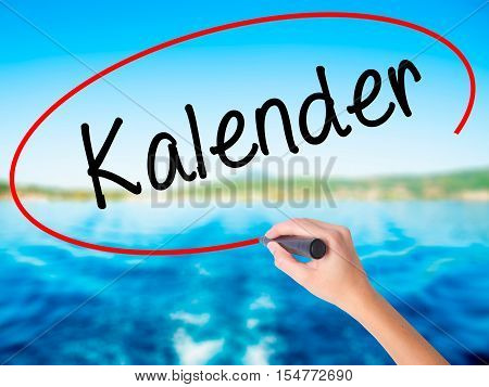 Woman Hand Writing Kalender (calendar In German)  With A Marker Over Transparent Board