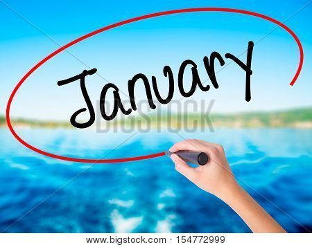 Woman Hand Writing January With A Marker Over Transparent Board
