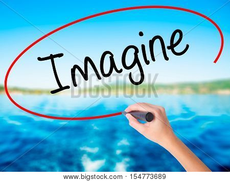 Woman Hand Writing Imagine  With A Marker Over Transparent Board