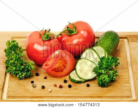 Cucumber and tomato on a wooden board