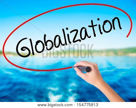 Woman Hand Writing Globalization With A Marker Over Transparent Board.