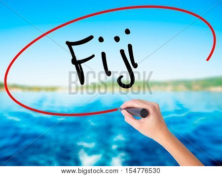 Woman Hand Writing Fiji  With A Marker Over Transparent Board.